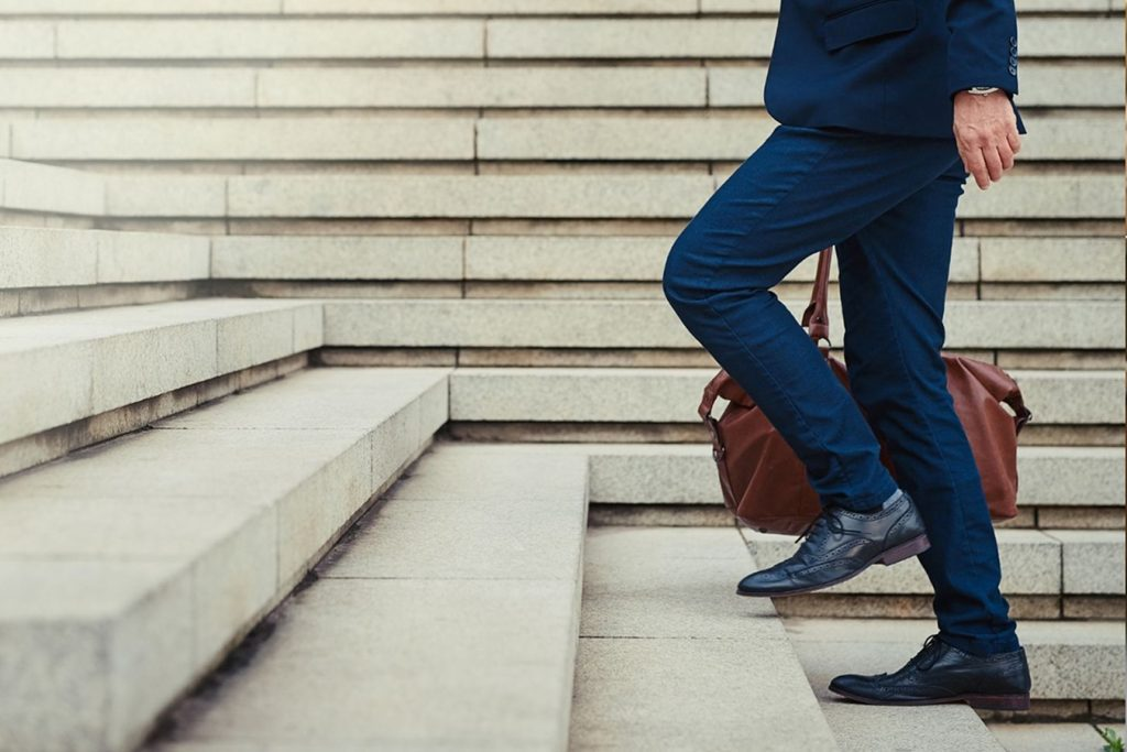 Man wearing blue business suit carrying brown briefcase walking up cement stairs outside. Rat race, getting ahead in business