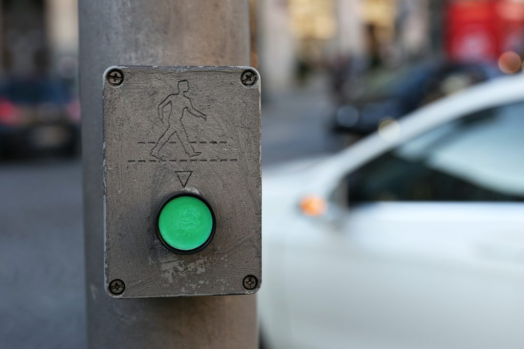 Green walk button at crosswalk of street at intersection in urban city car in background cross crossing the street